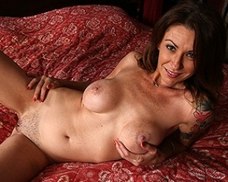 Cute American mom playing with her pussy on her bed