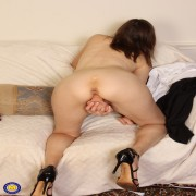 Naughty mature slut playing with her toys on the couch